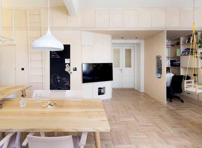 """""""Rozcestí"""" bytu: příchod z předsíně, vlevo kolem zkosené stěny s televizí směr kuchyně, vpravo průhled okénkem do pracovny"""