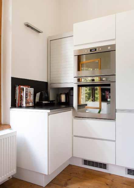 Za hliníkovou roletkou se schovají drobní kuchyňští pomocníci – rychlovarná konvice, toustovač a odšťavňovač.