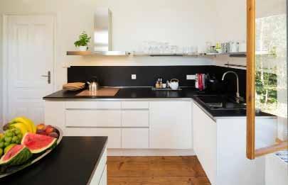 Provedení kuchyně v bílé a tmavě šedé odpovídá barevnosti celého interiéru. Za dveřmi se nachází nově vybudovaná komora.