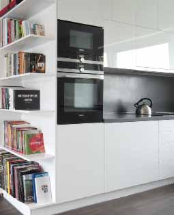 Na konci kuchyně má své místo otevřená knihovna s barevnými hřbety knih.